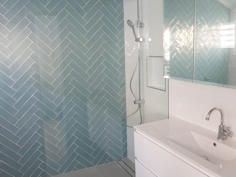 New Bathroom with blue tiles and white sink and grey tiles