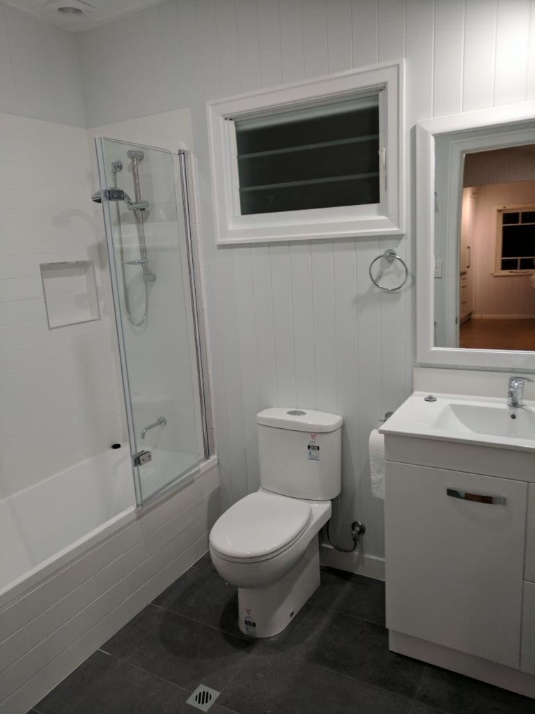 newly renovated bathroom with grey floor tiles and white walls
