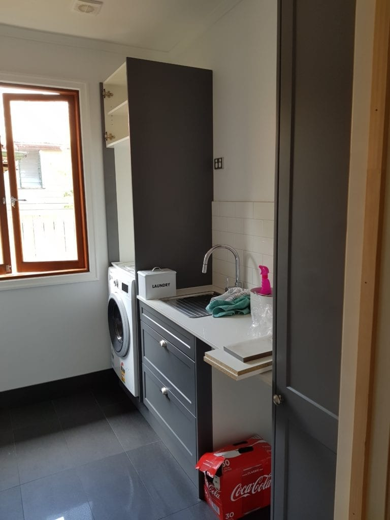 New laundry with grey cupboards and tiles