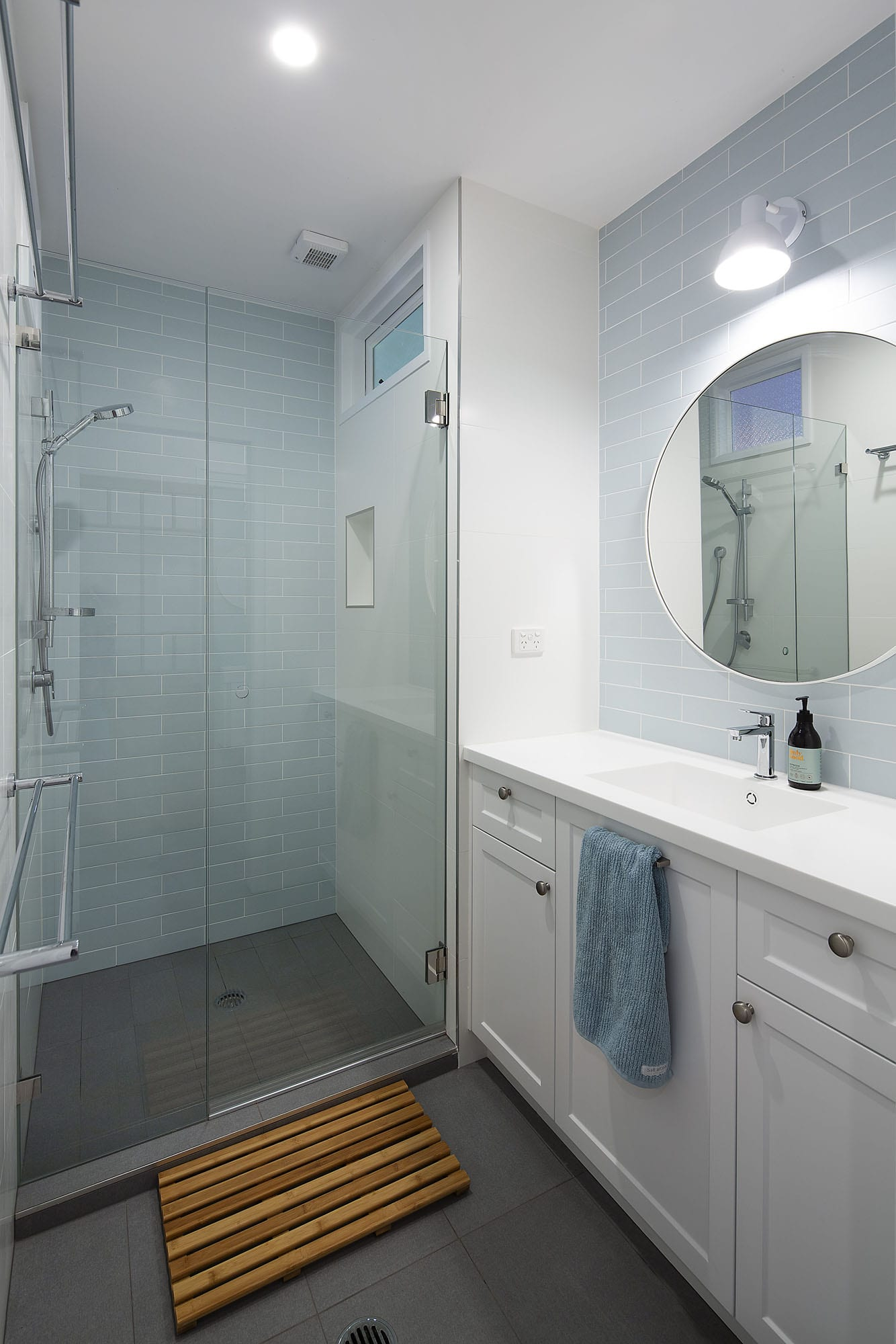 round mirror and large shower in renovated bathroom
