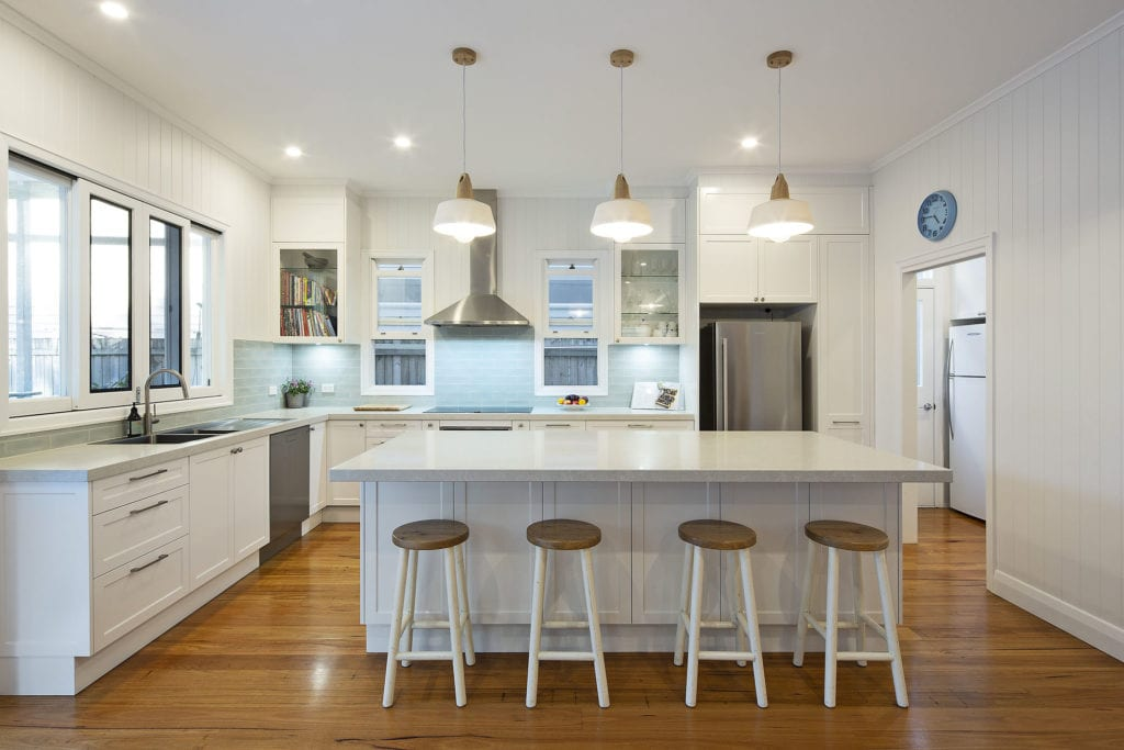 new kitchen with timber flooring, white benches and pendent lighting