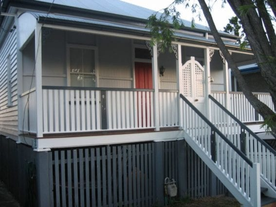 Raised queenslander with grey and white paint and a red door