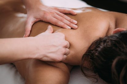 Physiotherapist massaging female patient with injured shoulder blade.  Sports injury treatment.
