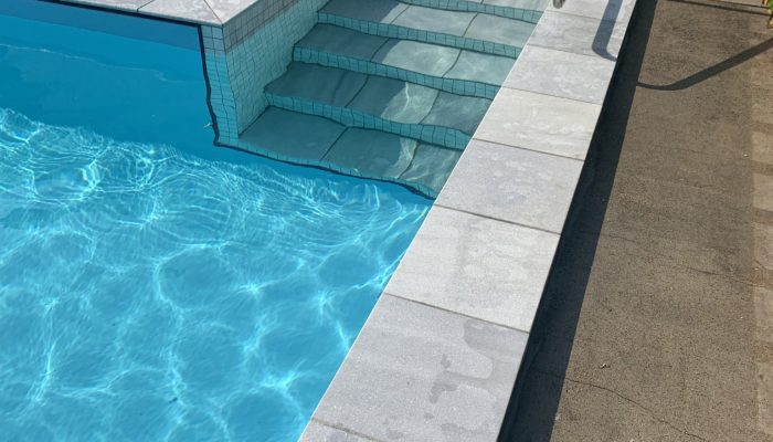 Block pool with Aqualux Light Blue with Parisan Blue Lime Stone coping and grey mosiac tiles.