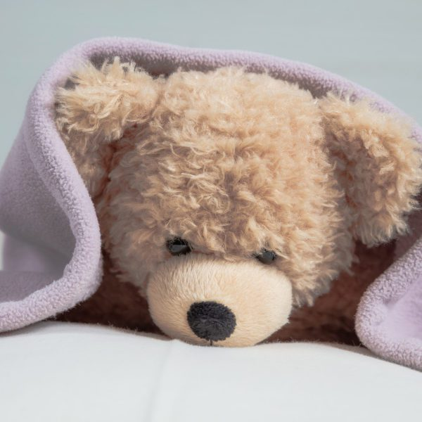 Kids bedtime, baby shower. Cute teddy laying on bed mattress covered with a towel
