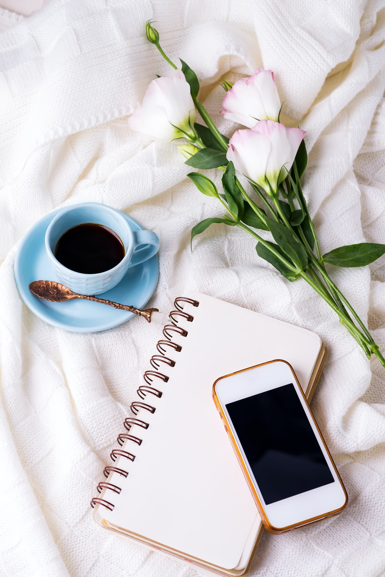 Having a cup of coffee with chocolate, flowers eustoma, notebook and phone on blanket in bed