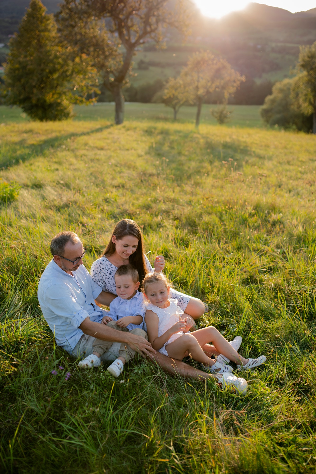 Young family with two small children sitting on meadow outdoors at sunset