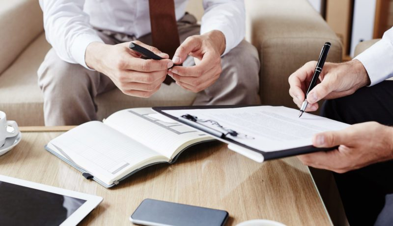Businessman pointing at contract while showing his partner where to sign it